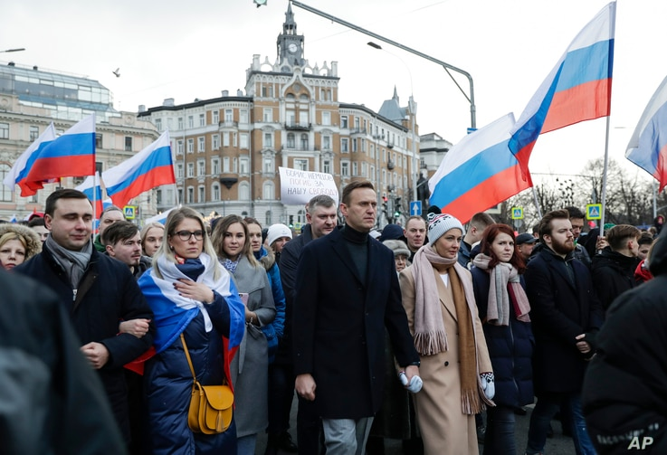Russian opposition activist Alexei Navalny, center, his wife Yulia, right of him, and opposition activist Lyubov Sobol, second…