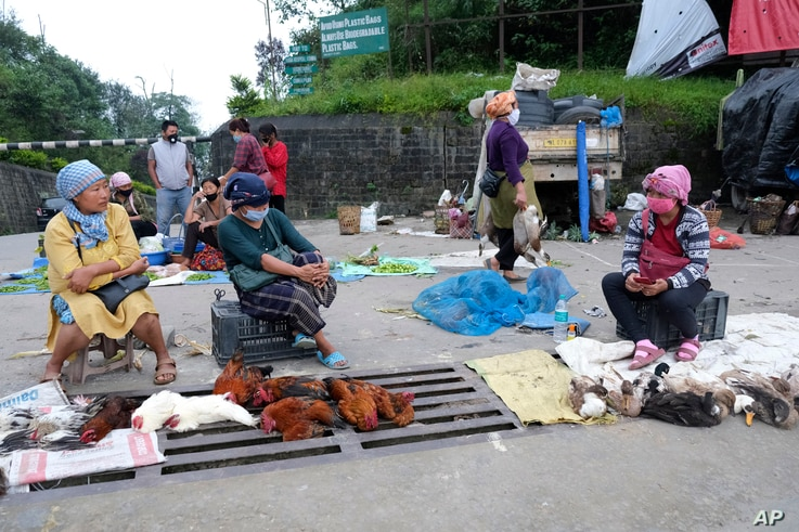 Naga women, wearing face masks as a precaution against the coronavirus, sit by the side of a road selling poultry on the eve of…