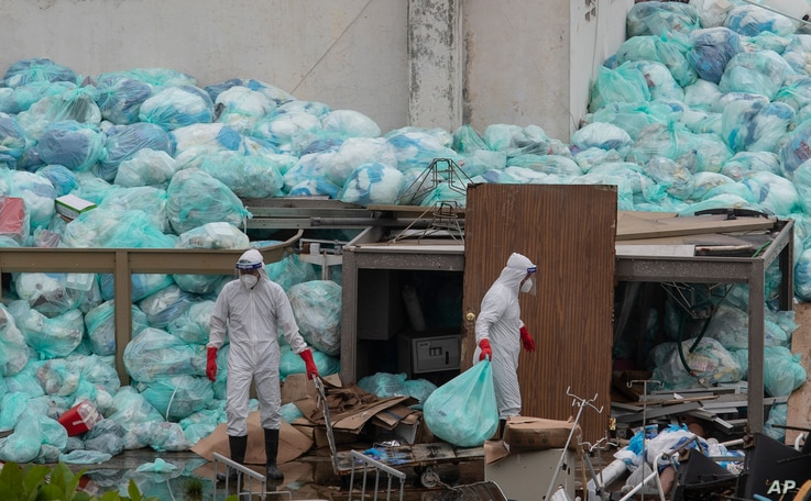Medical workers using protective equipment dispose of trash bags containing hazardous biological waste into a large pile…