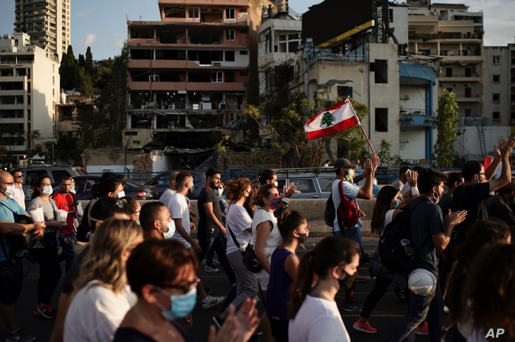 People march in honor of the victims of the last week's explosion that killed over 150 people and devastated the city, near the…