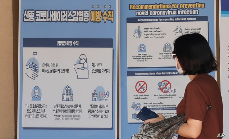 A visitor wearing a face mask walks near a banner showing precautions against the coronavirus at the Gyeongbok Palace, one of…