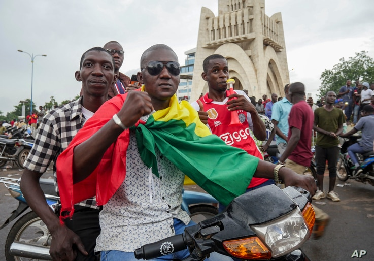 A man wears a national flag as he celebrates with others in the streets in the capital Bamako, Mali Tuesday, Aug. 18, 2020…