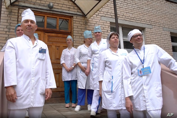 In this photo made from footage provided by the Russian Defense Ministry on Wednesday, July 15, 2020, medical workers look at…