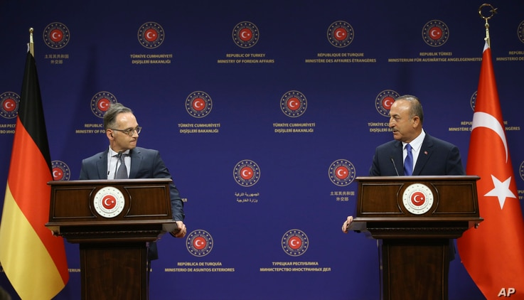 Turkey's Foreign Minister Mevlut Cavusoglu, right, and German counterpart Heiko Maas speak to the media after their talks, in…
