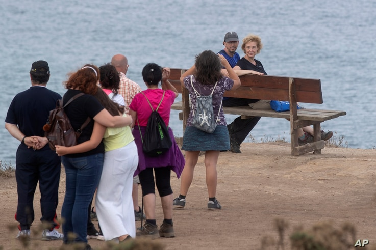 Tourists wait in line to sit on a bench on a cliff overlooking the Cantabrian sea in Loiba, north western Spain, Sunday, Aug. 2…