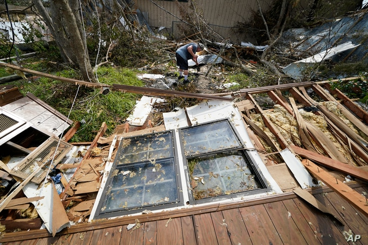 Bradley Beard digs as he searches in vain for his water shutoff valve, next to his heavily damaged home and the destroyed…