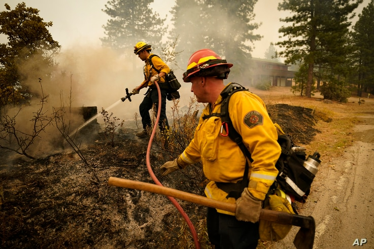 Tim Lesmeister, right, and Rick Archuleta, of the Clovis Fire Department, put out hotspots left behind by the Creek Fire…