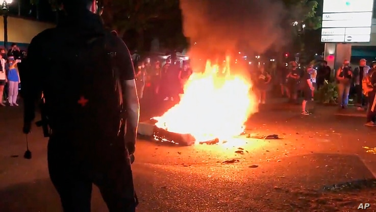 In this image taken from video a mattress burns in the street near the Portland Police Bureau's North Precinct Sunday night,…