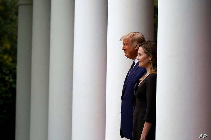President Donald Trump walks with Judge Amy Coney Barrett to a news conference to announce Barrett as his nominee to the…