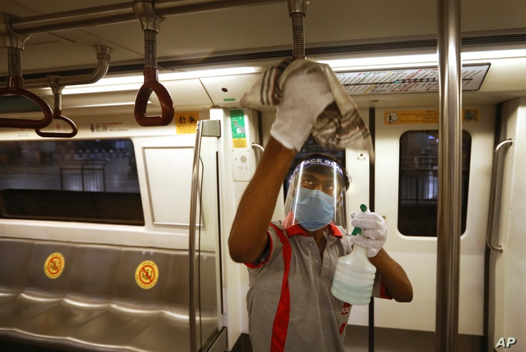 A workers sanitizes a metro coach in New Delhi, India, Thursday, Sept. 3, 2020. Delhi Metro will open for service in a phased…