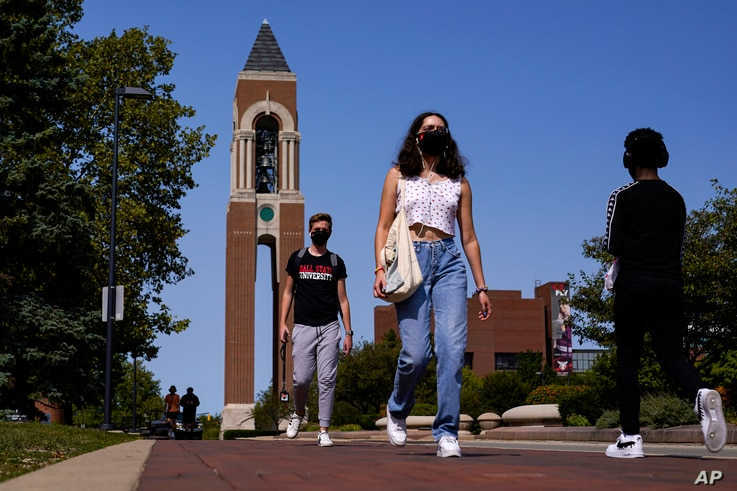 Masked students walk through the campus of Ball State University in Muncie, Ind., Thursday, Sept. 10, 2020. College towns…