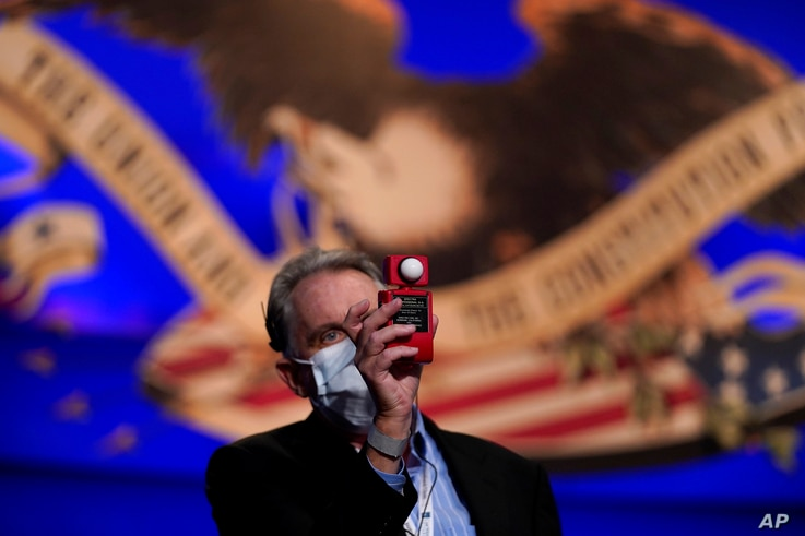 A member of the production team uses a light meter while on stage ahead of the first presidential debate between Republican…
