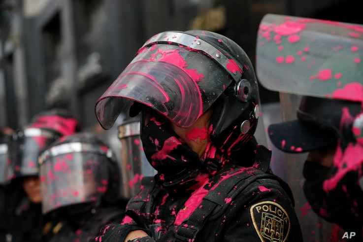 """Riot police get covered in red paint by abortion-rights demonstrators during the """"Day for Decriminalization of Abortion in…"""