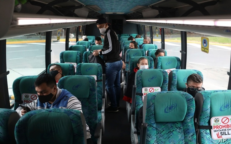 Passengers sit on a bus at the terminal for long-distance travel in Bogota, Colombia, Tuesday, Sept. 1, 2020. Airports, land…