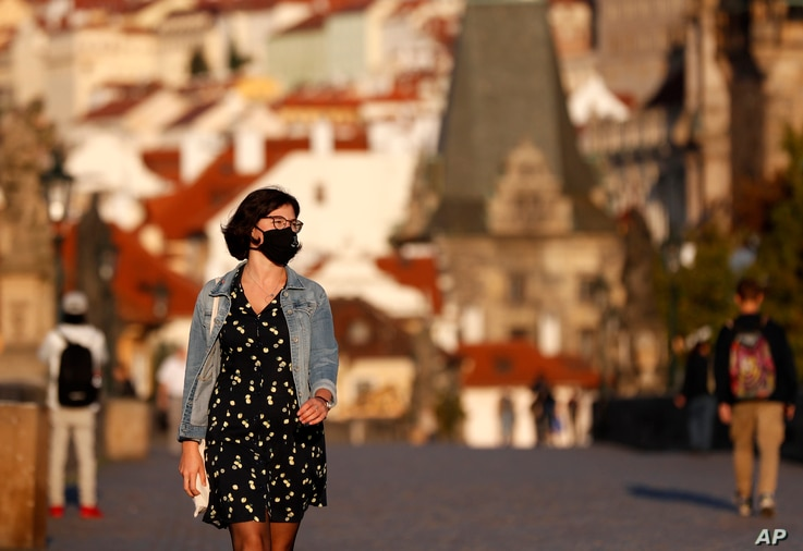 A young woman wearing a face mask walks across the medieval Charles Bridge in Prague, Czech Republic, Friday, Sept. 18, 2020…