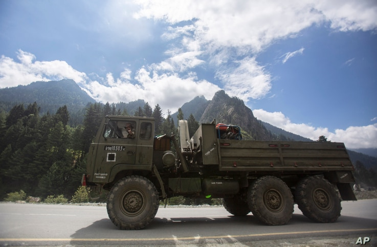 An Indian army soldier gestures towards the photographer as his convoy moves on the Srinagar- Ladakh highway at Gagangeer,…