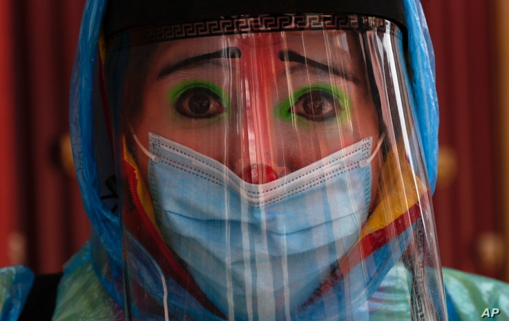 Clown Tapetito, wearing protective gear amid the new coronavirus, poses for a photo before disinfecting a home free of charge,…