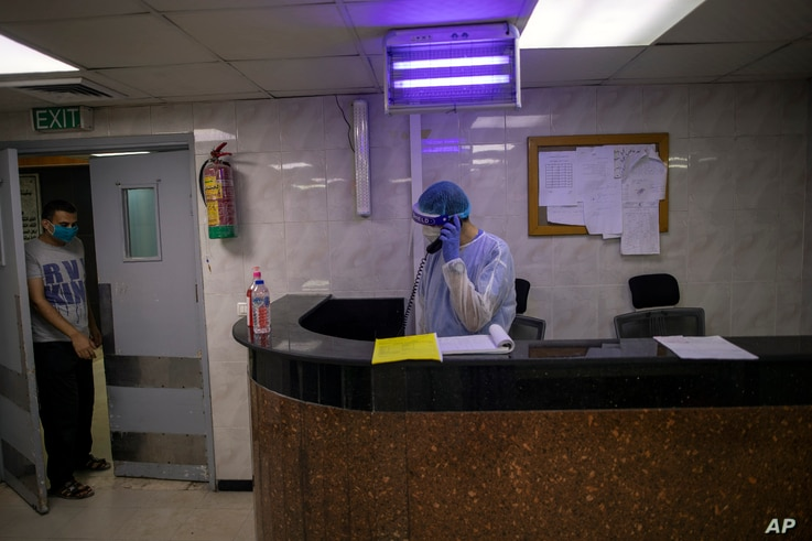 Palestinian doctors wear protective clothes as they work at the emergency room of the al-Quds Hospital in Gaza City, Monday,…