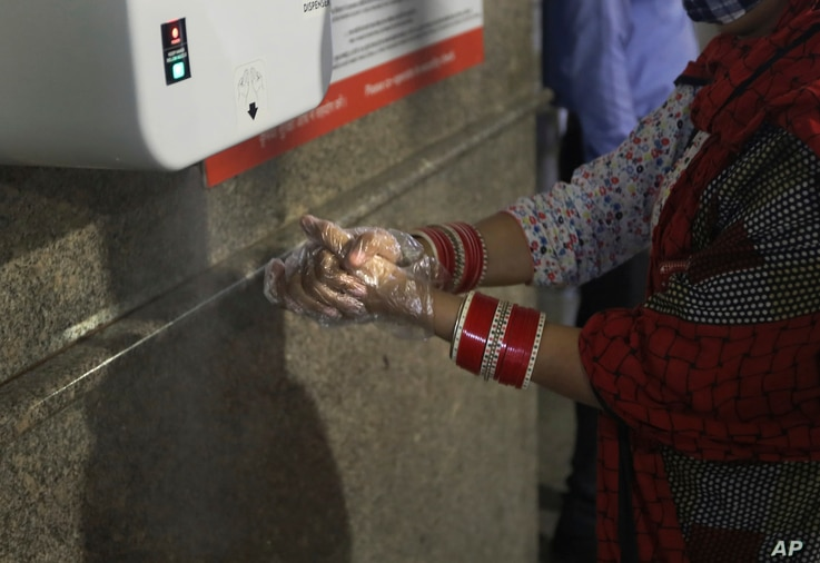 A woman sanitizes her hand at Delhi Metro station before boarding the train in Gurugram on the outskirts of New Delhi, India,…