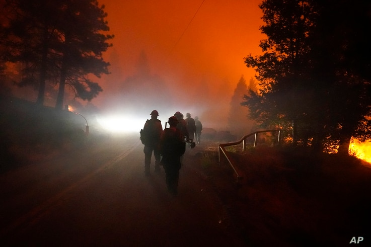 Members of the Laguna Hotshots, out of the Cleveland National Forest, walk on a road while fighting the Creek Fire, Sunday,…