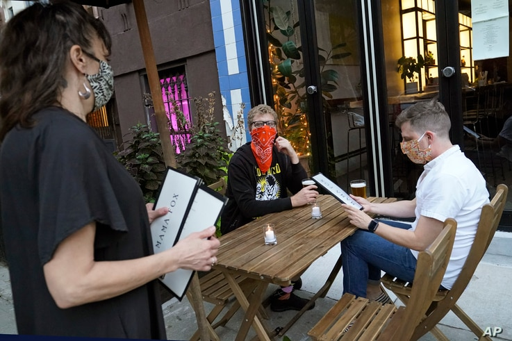 Owner Samantha DiStefano, left, prepares to hand menus to patrons and neighborhood regulars, Tuesday, Sept. 29, 2020, at her…