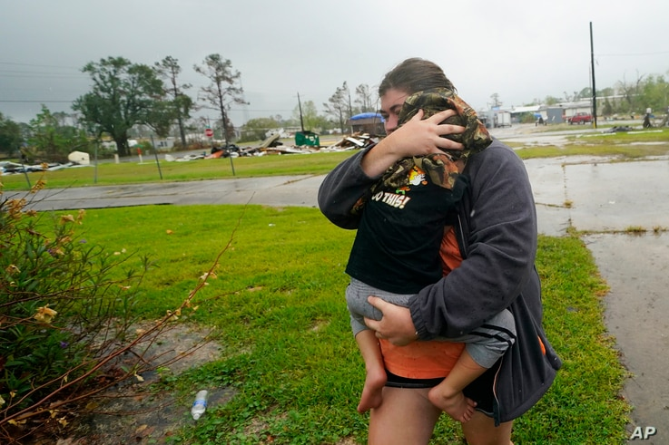 ADDS CITY - Danielle Fontenot runs to a relative's home in the rain with her son Hunter ahead of Hurricane Delta, Friday, Oct…