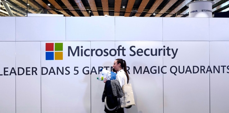 FILE - A woman walks in front of the Microsoft stand during the Cybersecurity Conference in Lille, northern France, Wednesday…
