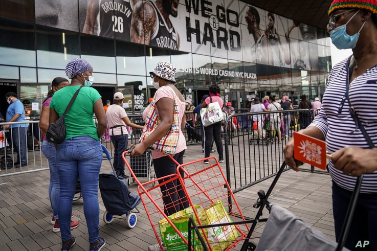 Residents wait in line to collect fresh produce and shelf-stable pantry items outside Barclays Center as Food Bank For New York…