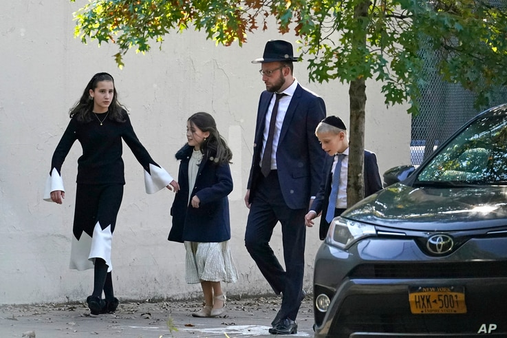 A man walks with his family, Sunday, Oct. 4, 2020, in the Borough Park neighborhood of New York. New York Gov. Andrew Cuomo…