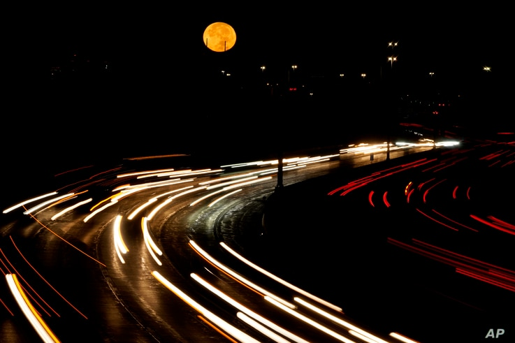 The full moon sets as morning traffic travels on a freeway Thursday, Oct. 1, 2020, in Leawood, Kan. (AP Photo/Charlie Riedel)