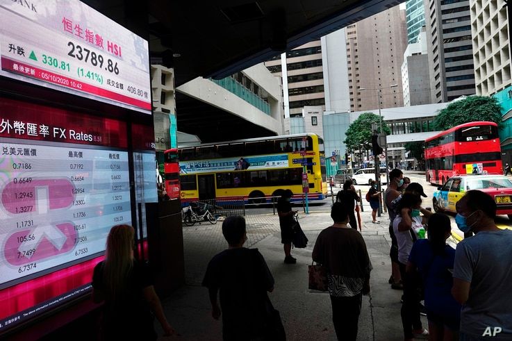People walk past a bank's electronic board showing the Hong Kong share index at Hong Kong Stock Exchange Monday, Oct. 5, 2020…