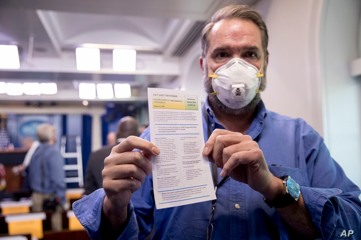 Journalist Brian Fuss holds up COVID-19 testing information after receiving a coronavirus test by the White House Medical Unit…