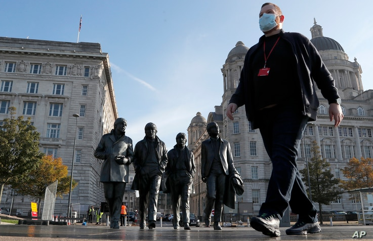 A man wearing a face mask walks past a statue of the Beatles, as new measures across the region are set to come into force in…