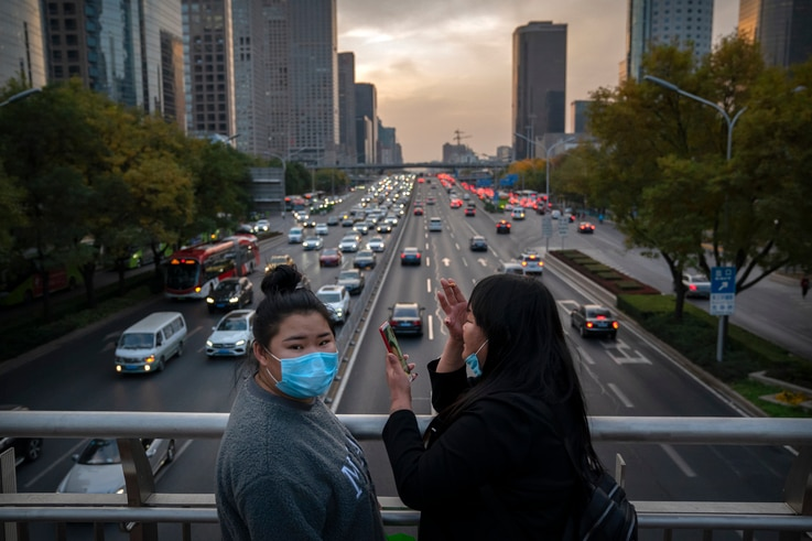 Women wearing face masks to protect against the coronavirus stand on a pedestrian bridge in Beijing, Friday, Nov. 13, 2020…