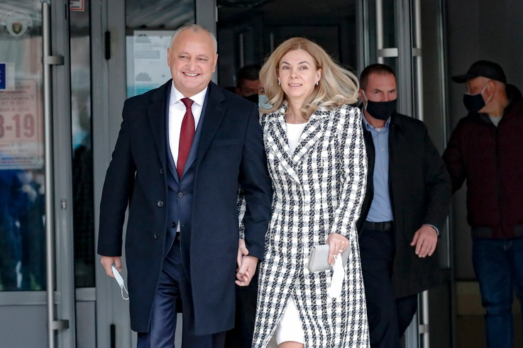 Incumbent Moldovan President Igor Dodon and his wife Galina smile while walking out of a voting station during the country's…