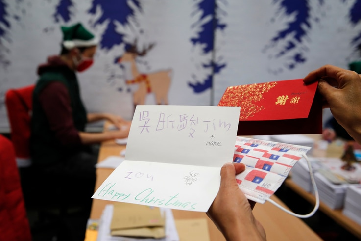"""A postal worker shows an envelope from Jim of Taiwan, who sent a face mask inside the letter he sent and wrote """"I (heart) U,""""…"""