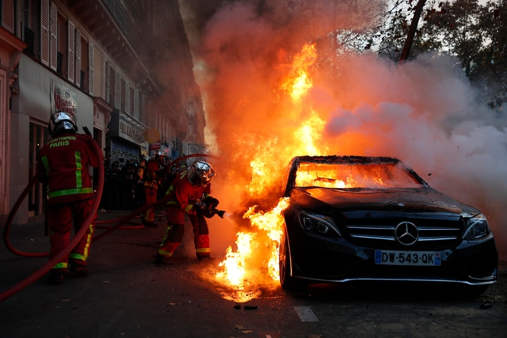 Fire-fighters pull off a fire on a burning car during a demonstration against a security law that would restrict sharing images…