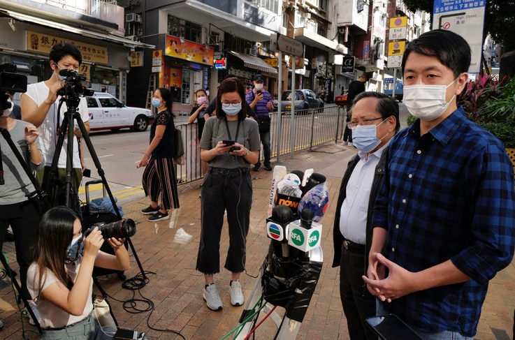 Pro-democracy legislator Ted Hui, right, talks to reporters outside a police station in Hong Kong Wednesday, Nov. 18, 2020…