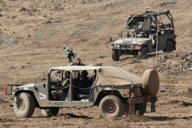 Israeli soldiers drive military vehicles during an exercise in the Israeli controlled Golan Heights near the border with Syria,…