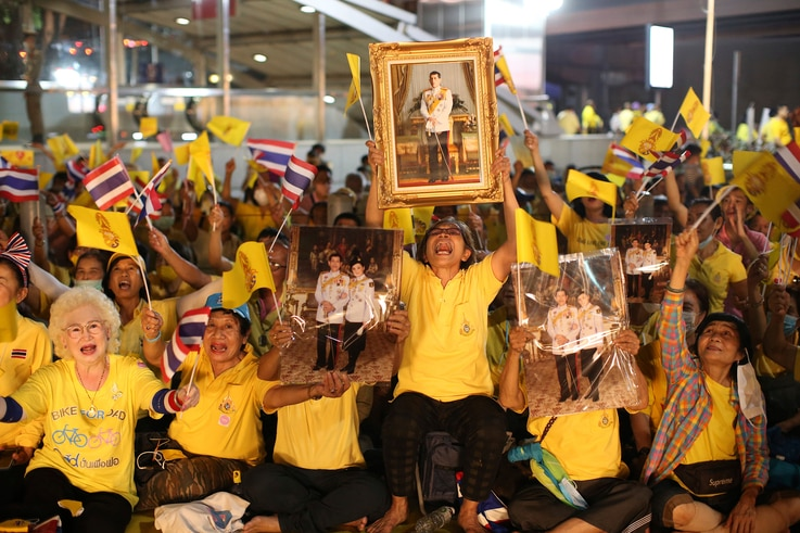 Supporter of the Thai monarchy hold images King Maha Vajiralongkorn and Queen Suthida at a ceremony to mark an anniversary of…