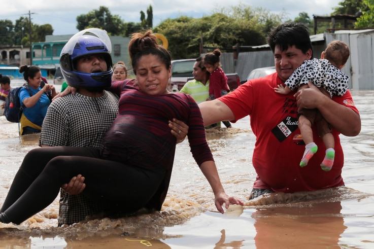 A pregnant woman is carried out of an area flooded by water brought by Hurricane Eta in Planeta, Honduras, Thursday, Nov. 5,…
