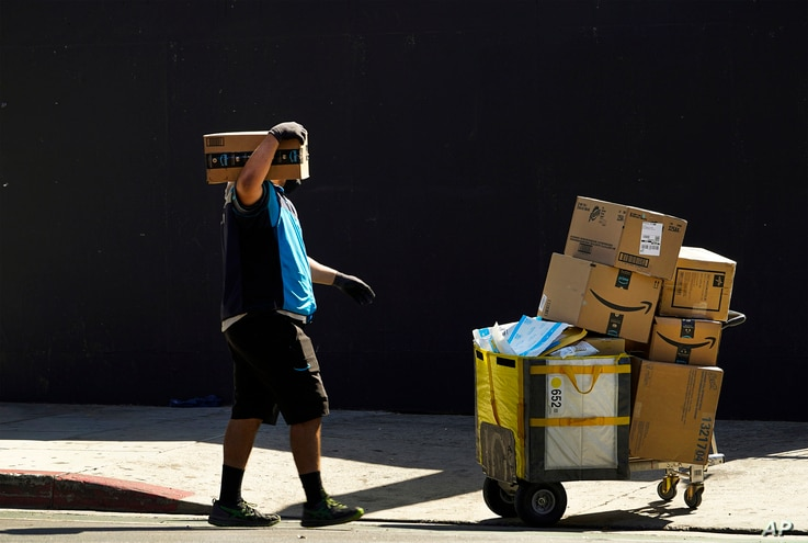 In this Thursday, Oct. 1, 2020, photo an Amazon worker wears a mask and gloves as he delivers boxes downtown Los Angeles…