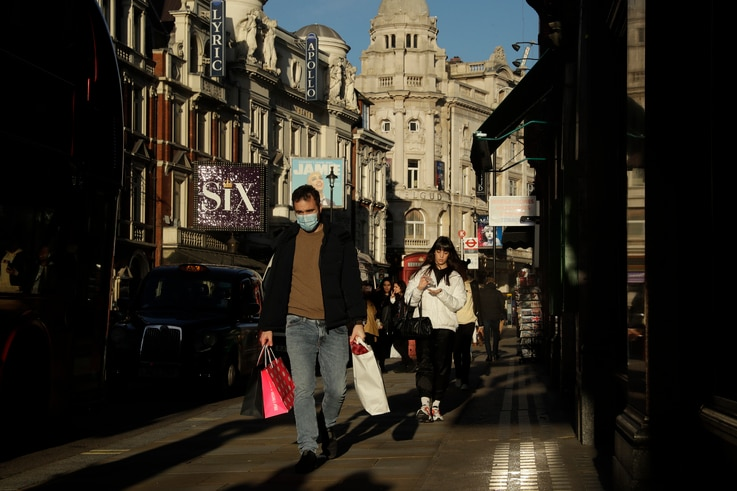 A man walks with shopping bags along Shaftesbury Avenue, in London, backdropped by theatres that have had to temporarily close…