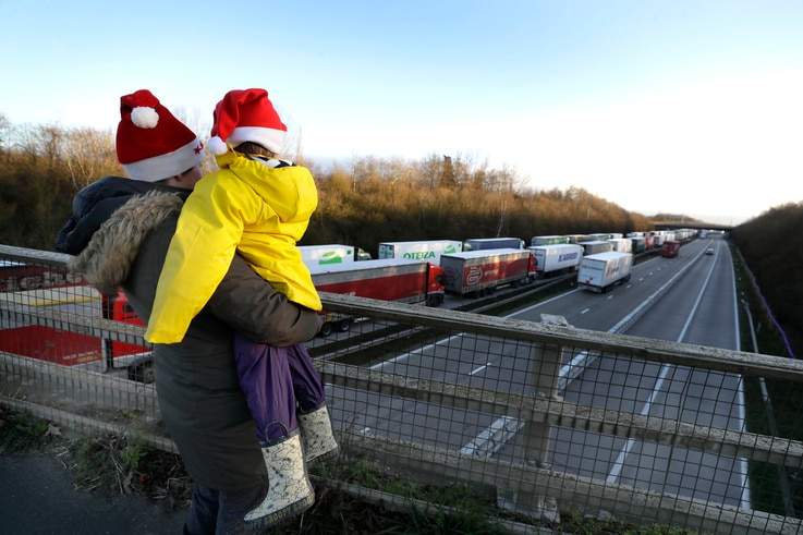A mother and child look at the line of trucks parked up on the M20, part of Operation Stack in Ashford, Kent, England, Friday,…