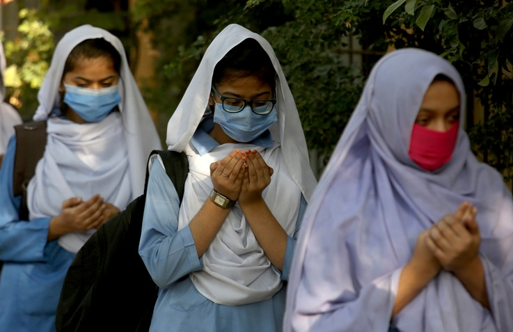 Students wearing face masks to prevent the spread of the coronavirus as they pray upon their arrival at their school, in…