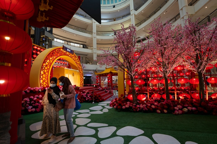 Two women take photos under the Chinese New Year lantern decorations at a shopping mall in Kuala Lumpur, Malaysia, on Saturday,...