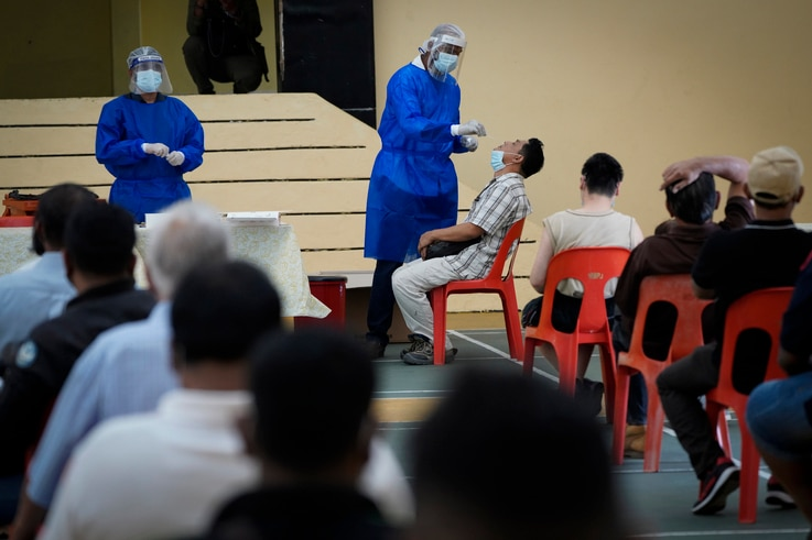 A medical worker collects a swab sample from a man during coronavirus testing in Petaling Jaya, Malaysia, Monday, Jan. 18, 2021...