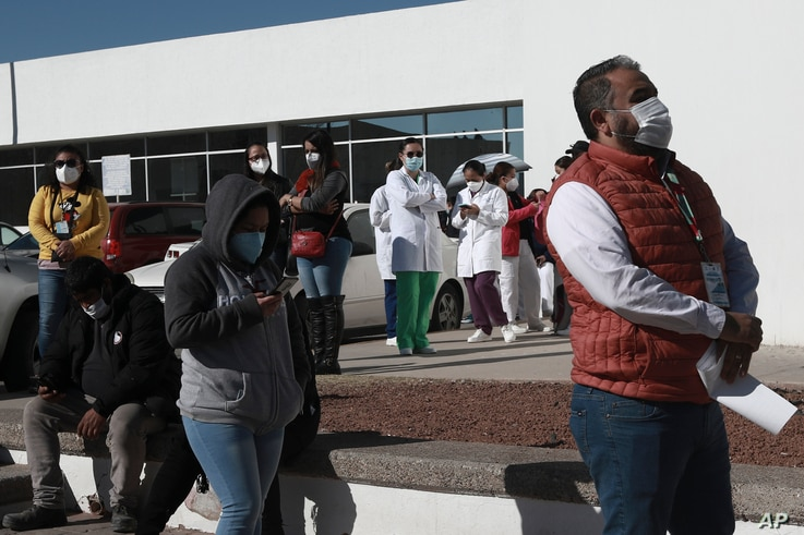 Health care workers wait in line outside General Hospital to receive the Pfizer COVID-19, on the first day of coronavirus…