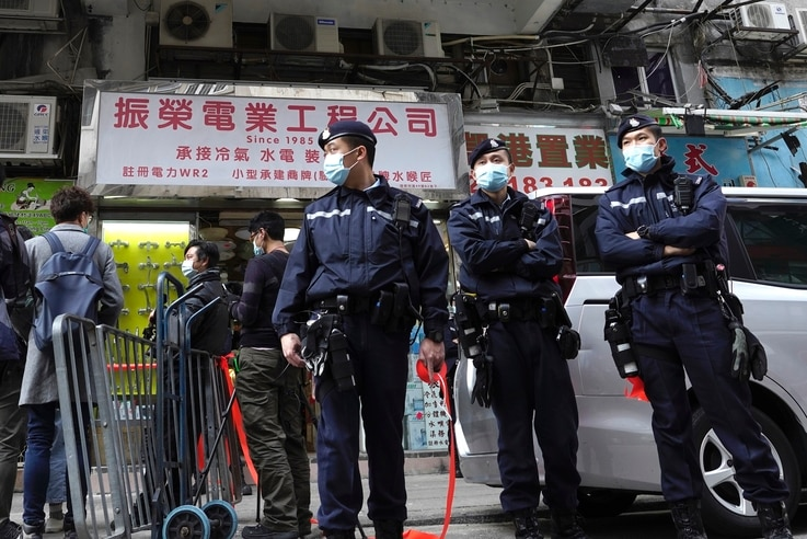 Police officers stand guard outside office of District councillor and lawyer Daniel Wong Kwok-tung, while police search in Hong…