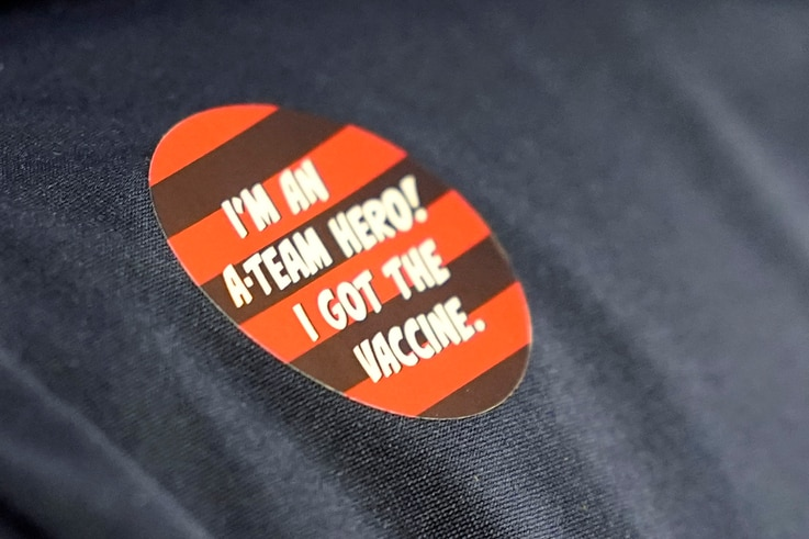 """A worker at Queen Anne Healthcare, a skilled nursing and rehabilitation facility in Seattle, wears a sticker that reads """"I'm an…"""